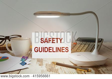 Office Desk With A Lamp That Illuminates The Inscription Safety Guidelines