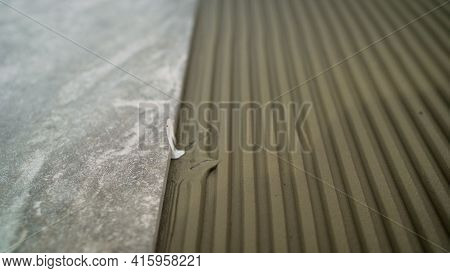 Construction Worker Tiler Is Tiling, Tiler Installing Ceramic Tiles On A Floor. Industrial Tiler Lay