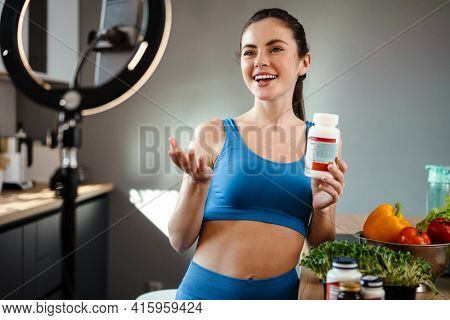 White young woman taking selfie footage with supplement on mobile phone at home kitchen