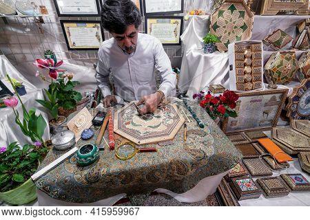 Shiraz, Iran - 04.10.2019: Iranian Khatam Master Woking Behind The Desk In His Shop In Shiraz, Iran.
