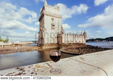 Glass Of Red Wine On Wall Of The 16th-century Fortification Belem Tower On Sunny Riverbank. Lisbon.