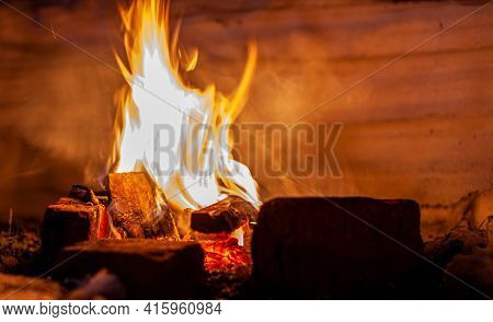 A Campfire Burns In The Snow At Night In The Snow In The Cold Winter. The Flame Of The Fire Warms An