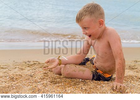 A Caucasian Boy Sits On A Beach By The Sea In Summer And Flattens Pebbles In The Sand In Order To Th