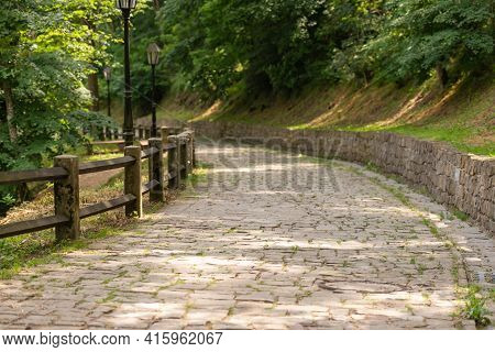 A Stone Paved Path Leading Down From The Mountain. Stone Path And Wall. Wooden Fence Made Of Thick B