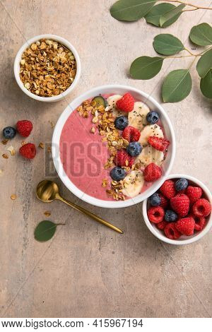 Summer Acai Smoothie Bowls With Raspberries, Banana, Blueberries, And Granola On Gray Concrete Backg