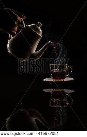 Pouring Black Hot Tea Into The Cup Stock Photo.on Black Background.