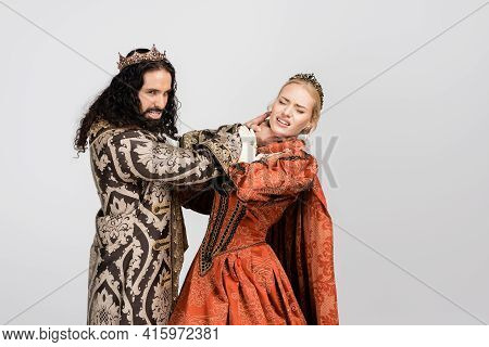 Hispanic King In Medieval Clothing Choking Scared Queen In Crown Isolated On White.