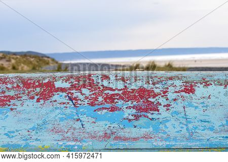 Abstract Paint Effect On Wooden Boat With View Of A Beach In The Background
