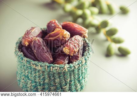 Very nutritious ripen dates stored in a tiny basket placed along with bunch of green dates. Best quality dates from Saudi.