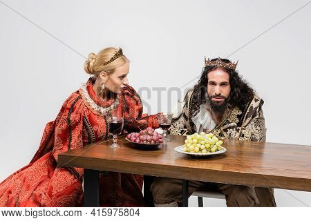 Blonde Queen Looking At Poisoned Hispanic King In Medieval Clothing Choking Isolated On White.