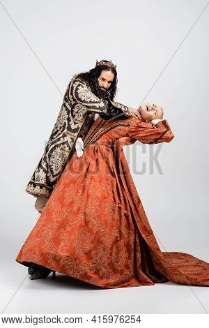 Full Length Of Cruel Hispanic King In Medieval Clothing Choking Shocked Queen In Golden Crown On Whi