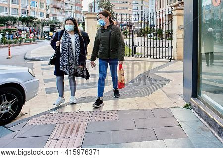 Antalya, Turkey - March 19, 2021: Two Women In Protective Face Masks Rush To Get Home Before Curfew