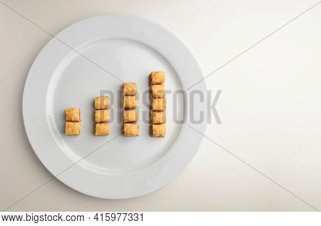Pieces of Baklawa arranged on a white plate like a upward statistics graph. A concept for growth of confectionary or bakery business.
