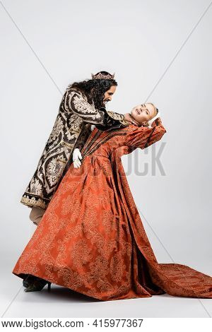 Full Length Of Cruel Hispanic King In Medieval Clothing Choking Blonde Queen In Golden Crown On Whit
