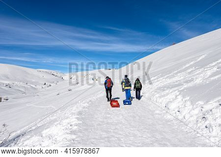 A Group Of Hikers With Backpacks And Bobs Walking On A Snowy Footpath On Lessinia Plateau, Regional