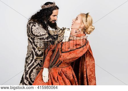 Cruel Hispanic King In Medieval Clothing Choking Shocked Queen In Golden Crown Isolated On White.