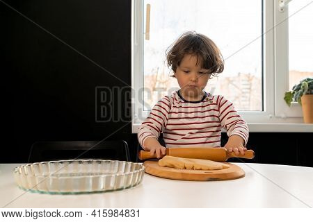 Little Kid Preparing A Cake And Rolling Out The Dough With A Rolling Pin On The Kitchen Table