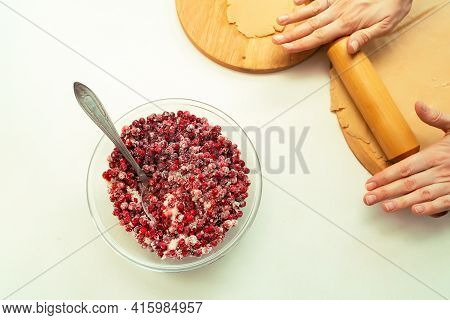 Human Hands Rolling Out The Dough With A Wooden Rolling-pin On The Board For Preparing A Pie With Be