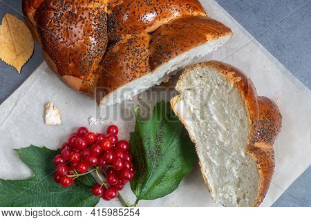 On The Table Is A Sliced Loaf Of White Bread With A Crisp Crust Sprinkled With Poppy Seeds. Next To