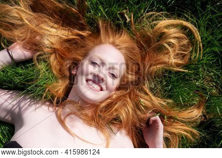 Beautiful Portrait Of A Young Sexy Red-haired Woman, Laughing, Lying In The Spring, Summer Sun, Rela