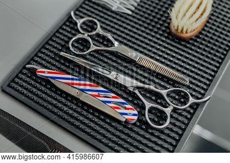 Barbershop Equipment: Scissors And Razor. Close-up Hairdresser Tools. Selective Focus
