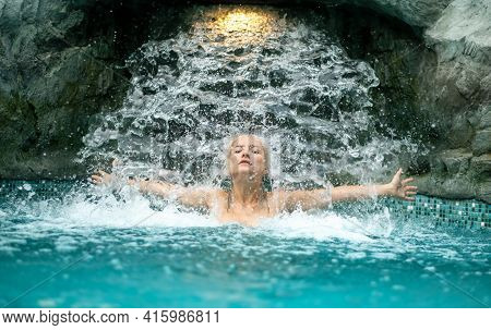 Beautiful Young Cute Sexy Blonde Woman With Arms Stretched To The Side Under The Splashing Water Of