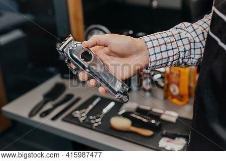 Barber Holding Electric Razor. Barbershop Equipment. Close-up Hairdresser Tools. Selective Focus