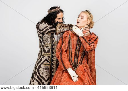 Hispanic King In Medieval Clothing Choking Shocked Queen In Golden Crown Isolated On White.