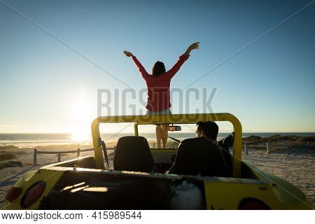 Happy caucasian couple on beach during sunset woman sitting on beach buggy man sitting in. beach break on summer holiday road trip.