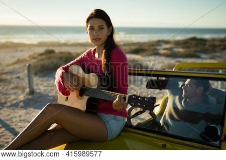 Caucasian woman sitting on beach buggy playing guitar, man sitting behind steering wheel. beach break on summer holiday road trip.