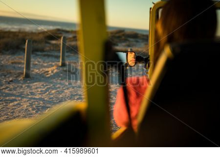 Caucasian woman sitting in beach buggy by the sea during sunset reflected in mirror. beach break on summer holiday road trip.