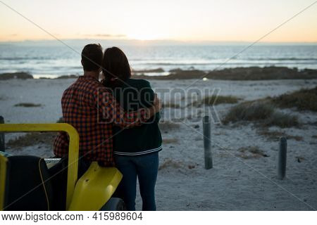 Happy caucasian couple leaning against beach buggy by the sea during sunset embracing. beach break on summer holiday road trip