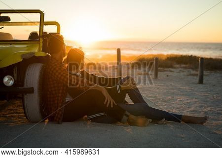 Happy caucasian couple leaning against beach buggy by the sea watching sunset. beach break on summer holiday road trip.