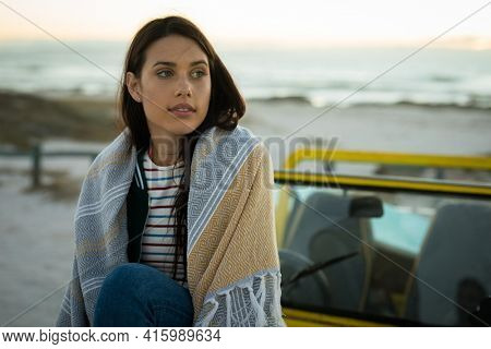 Happy caucasian woman sitting on beach buggy by the sea wearing shawl looking ahead. beach break on summer holiday road trip