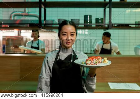 Portrait Of Smiling Waitress Wearing Apron Looking At Camera, Holding A Plate With Sushi Rolls. Japa