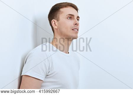 Pensive handsome man stands leaning against a white wall. Athletic man posing at studio. Men's health.