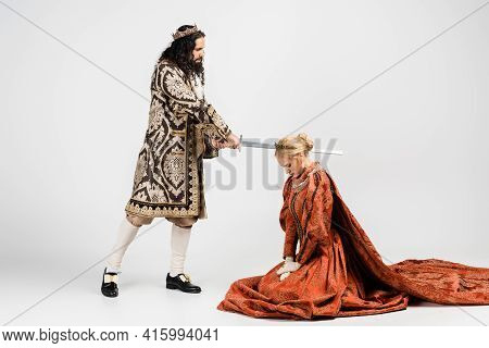 Full Length Of Cruel Hispanic King In Medieval Clothing Holding Sword Near Scared Queen In Crown On