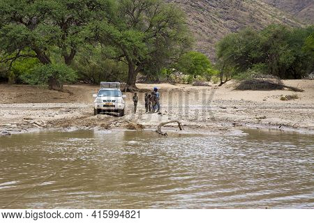 Kaokoland, Namibia, January 10: 4x4 Waiting In Front Of A River To Cross And Young Black African Kid