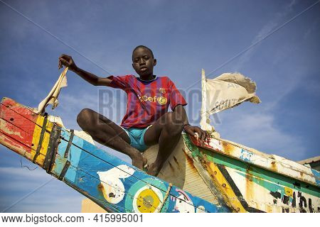 Saint-louis, Senegal, Dec 4: African Young Kid Sitting On A Colored Fisher Boat With Unicef T-shirt