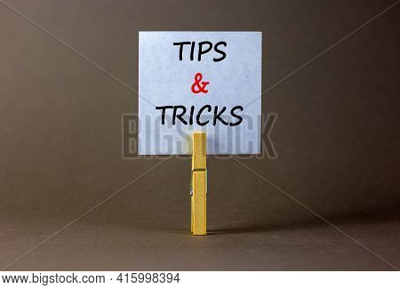 Tips And Tricks Symbol. White Paper On Wooden Clothespin. Words 'tips And Tricks'. Beautiful Grey Ba