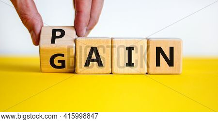 Pain Or Gain Symbol. Businessman Turns The Wooden Cube And Changes The Word Pain To Gain. Mindset Fo