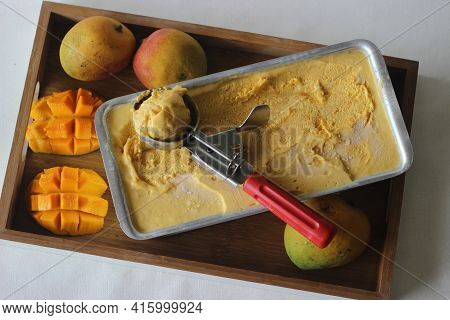 Scooping Of Mango Ice Cream For Serving From A Tray Kept Outside From Freezer