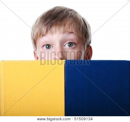 Closeup of a cute blond boy looking from behind two colorful hardcover books surprised (isolat