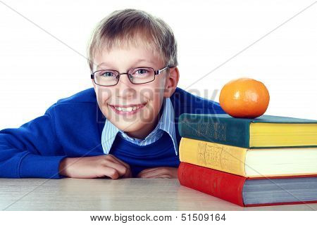 Beautiful schoolboy sitting at a table with a stack of colorful books and a tangerine laughing