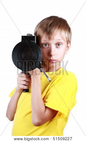 Beautiful joyful blond boy in a yellow t-shirt holds a vintage motion picture camera
