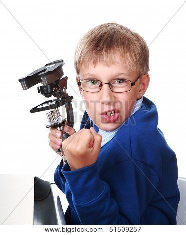 Enraged blond boy in a blue sweater holding a microscope and menacing with his fist