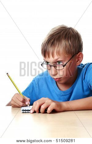 Happy cute blond boy in a blue t-shirt sitting at a table drawing in a notepad with a pencil (isolat