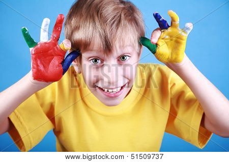 Beautiful cheerful blond boy in a yellow t-shirt shows multicolored painted hands and smiles