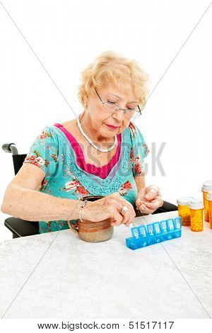 Senior woman in wheelchair sorting her medication for the week.  White background.