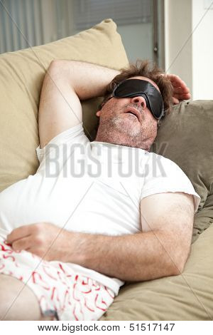 Lazy, unemployed man asleep on the couch, unshaven and in his underwear.
